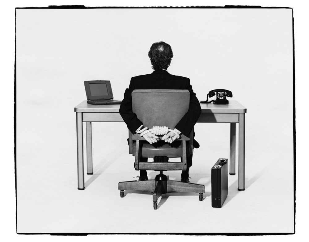 corporate-america-businessman-tied-to-desk_pop_13595
